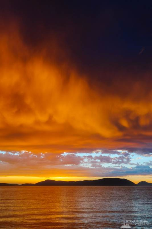 A landscape photograph of the sunset lighting up the storm clouds and water over Rosario Strait as viewed from Washington Park in Anacortes, Washington.