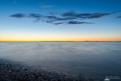 A long exposure photograph of the last sunset of the summer from the shores of Joseph Whidbey State Park near Oak Harbor, Washington