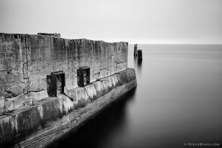 A black and white photograph of old concrete ruins from the Dickman Mill along the Puget Sound in Tacoma, Washington.