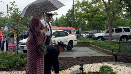 Officer Hajrudin Ducanovic lays flowers on his sister's memorial Saturday, May 16, 2015 in the Bevo Mill neighborhood of south St. Louis. His commanding officer Captain Steven Mueller and his wife Edina Ducanovic look on.