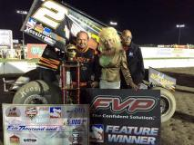 """Danny Lasoski poses in Victory Lane with """"Sandy is Dolly"""" and flagman Doug Clark Thursday at I-80 Speedway"""