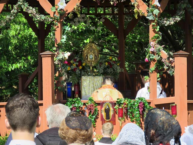 Fr. Casimir kneels before the Blessed Sacrament exposed on the outdoor altar