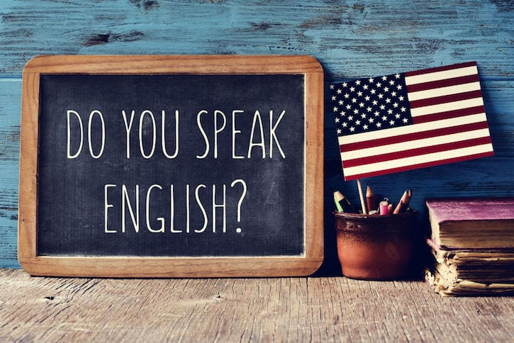 63892262 - a chalkboard with the question do you speak english? written in it, a pot with pencils and the flag of the united states, on a wooden desk