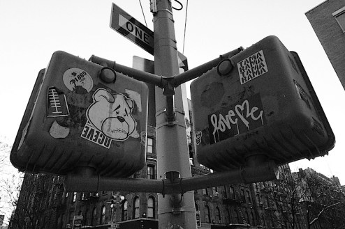 a bear sticker and a love me sticker on a walk signal in NYC
