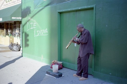graffiti that reads die living as a saxaphone player plays on the streets of NYC