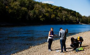 Lamb and students look through rocks and soil on the shore of the Mississippi River.