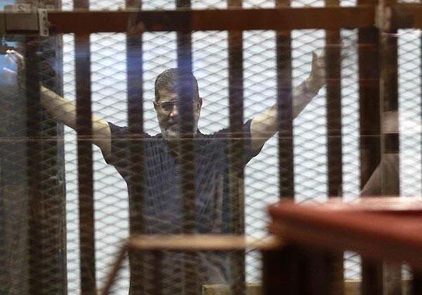 بالفيديو: شاهد ماذا فعل مرسي بقفص الاتهام قبل دقائق من الحكم عليه