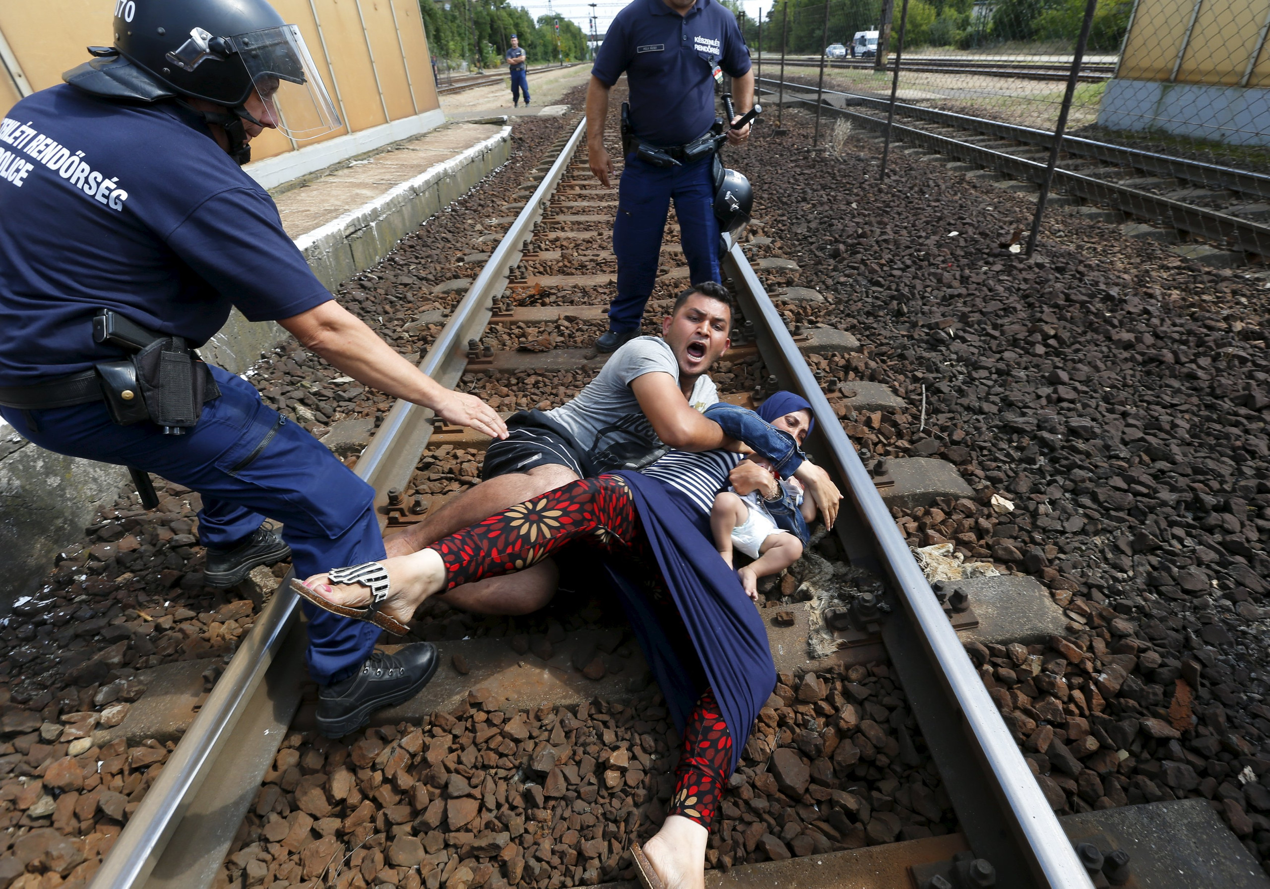 """Hungarian policemen stand by the family of migrants as they wanted to run away at the railway station in the town of Bicske, Hungary, September 3, 2015. REUTERS/Laszlo Balogh     SEARCH """"YEAREND 2015: MIGRANT CRISIS"""" FOR ALL 55 PICTURES"""