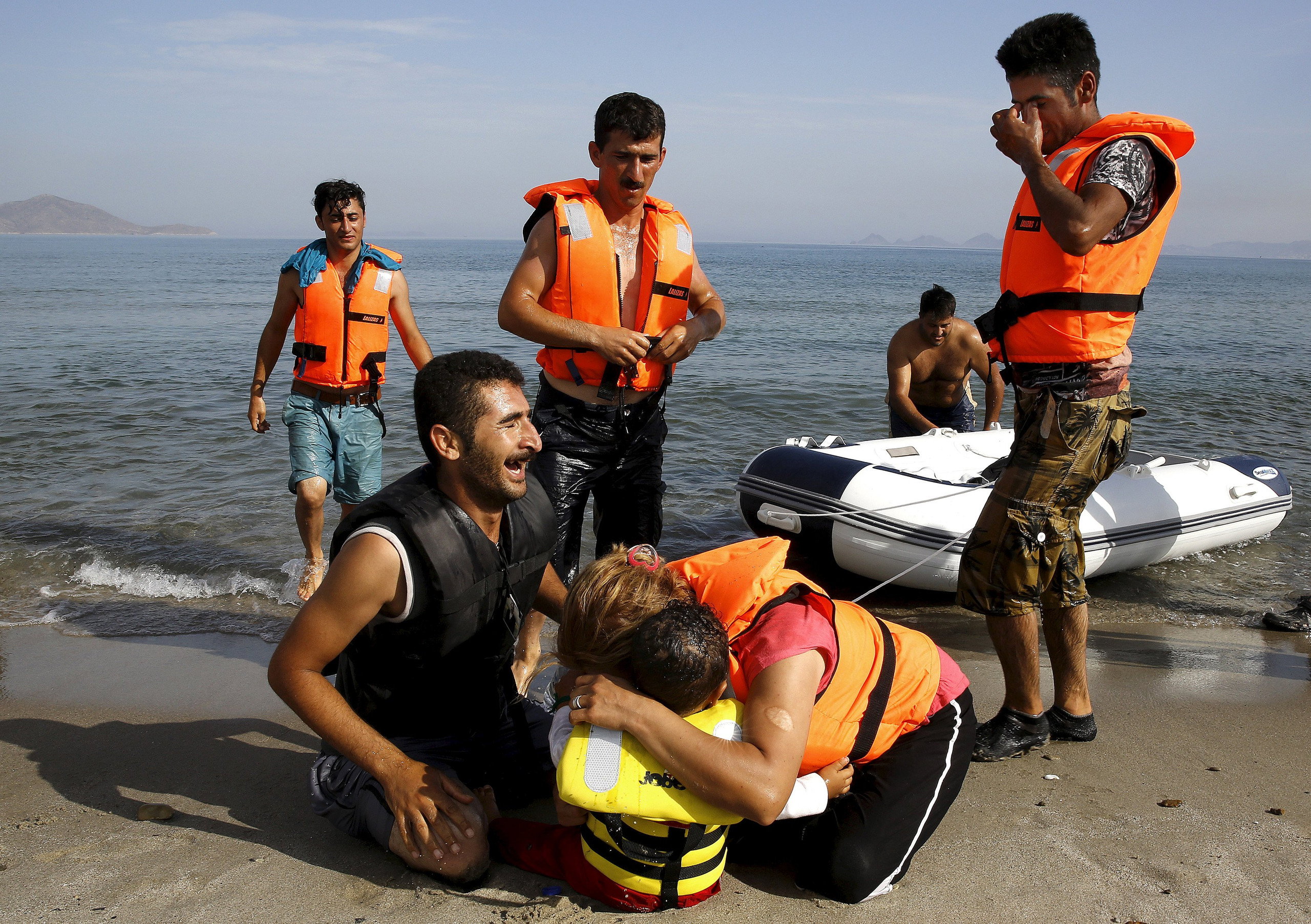 """An Iranian migrant cries next to his son and wife moments after a small group of exhausted migrants from Iran arrive by paddling an engineless dinghy from the Turkish coast (seen in the background) at a beach on the Greek island of Kos August 15, 2015.  REUTERS/Yannis Behrakis     SEARCH """"YEAREND 2015: MIGRANT CRISIS"""" FOR ALL 55 PICTURES"""