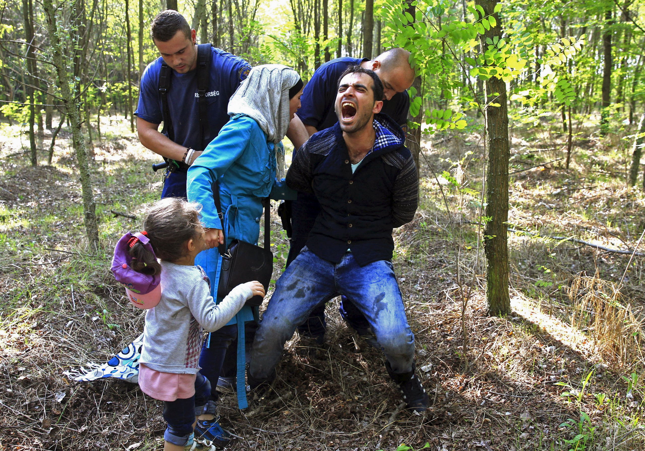 """Hungarian policemen detain a Syrian migrant family after they entered Hungary at the border with Serbia, near Roszke, August 28, 2015. REUTERS/Bernadett Szabo          SEARCH """"YEAREND 2015: MIGRANT CRISIS"""" FOR ALL 55 PICTURES"""