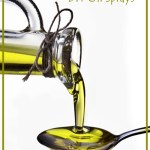 Olive oil flowing from carafe into the spoon.