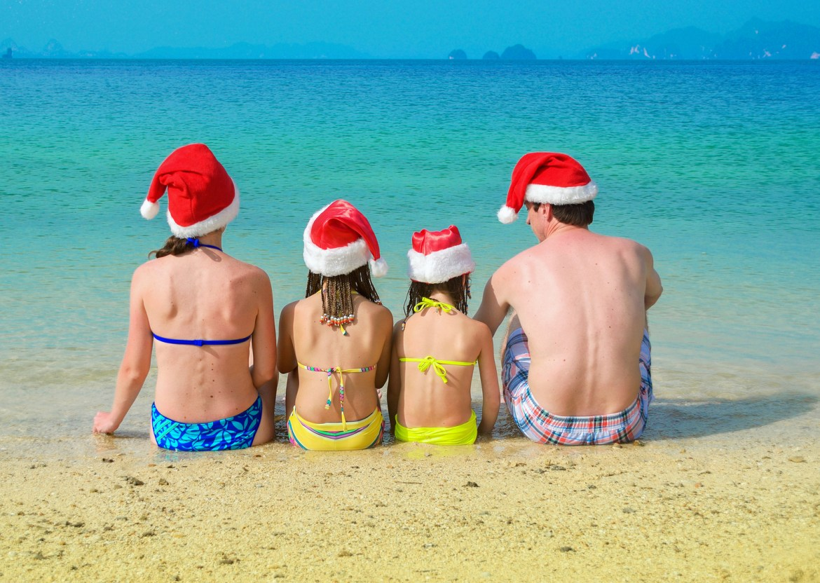 Family in santa hats having fun on beach vacation, new year and christmas holiday concept