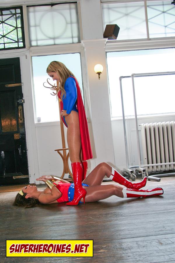 Supergirl standing over Wonder Woman