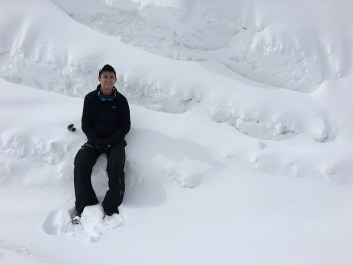 Eric sitting in some snow at the top.