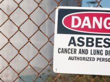 Danger sign on fence warning of potential exposure to asbestos used to depict article about two workers exposed to asbestos