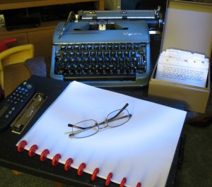 Photo of a typewriter, cards, and a notebook