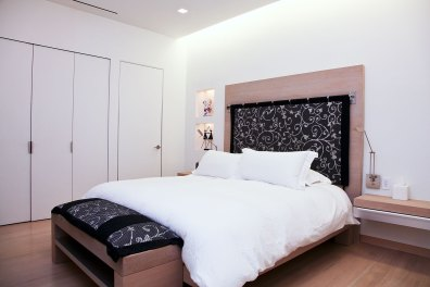 Bedrooom - A recessed light at the head of bed gives off a nice glow, as do the combination of sixteen other recessed lights. Special aluminum jams and recesses frame the doors. Bed and nightstands were built for the space.