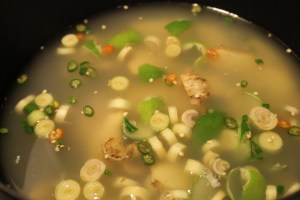 The broth, lime juice, lime peel, ginger, lemongrass, and chiles in the saucepan.