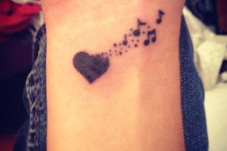 heart turning into music notes tattoo on wrist