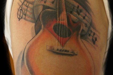 guitar with music notes tattoos