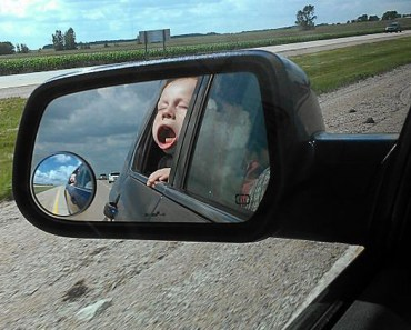 Baby in side view mirror, wind blowing out cheecks