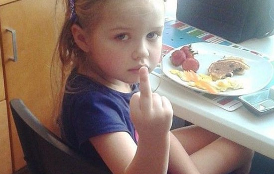 Funny awkward family photo of girl at dinner table giving the finger to the camera