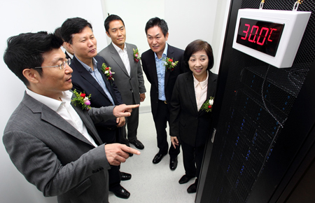 Lee Hee-sung, second from right, country manager of Intel Korea, and Song Jung-hee, to his right, senior executive vice president of KT's service innovation division, listen to Yun Dong-sik, head of KT's cloud division, at a high-temperature ambivalence test center jointly built by the two firms in Cheonan, South Chungcheong Province, Tuesday. / Courtesy of KT