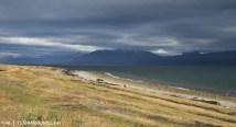 Threatening dark clouds over a sunlit beach