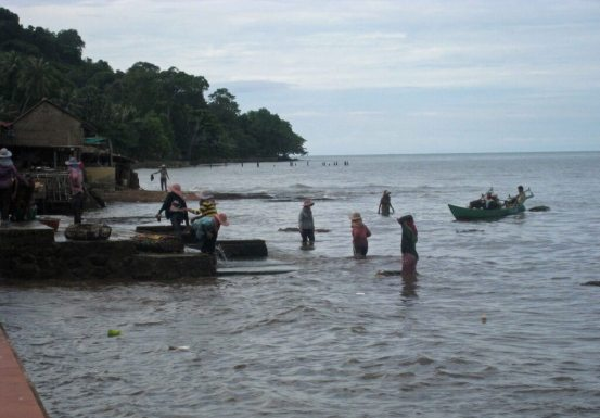 Women of Kep bringing in the crab baskets, first catches of the day