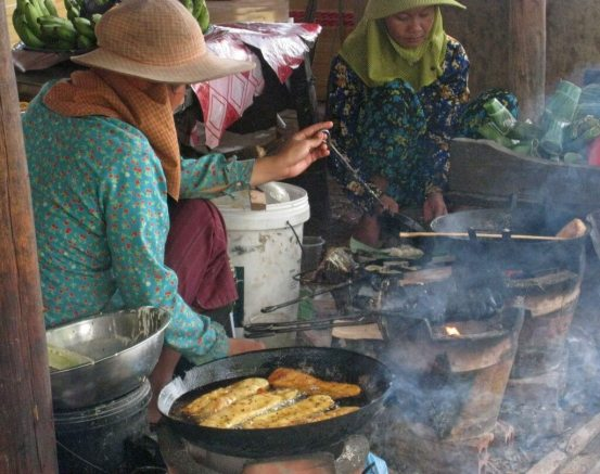 Women of Kep cooking fish at seafood market, beachside