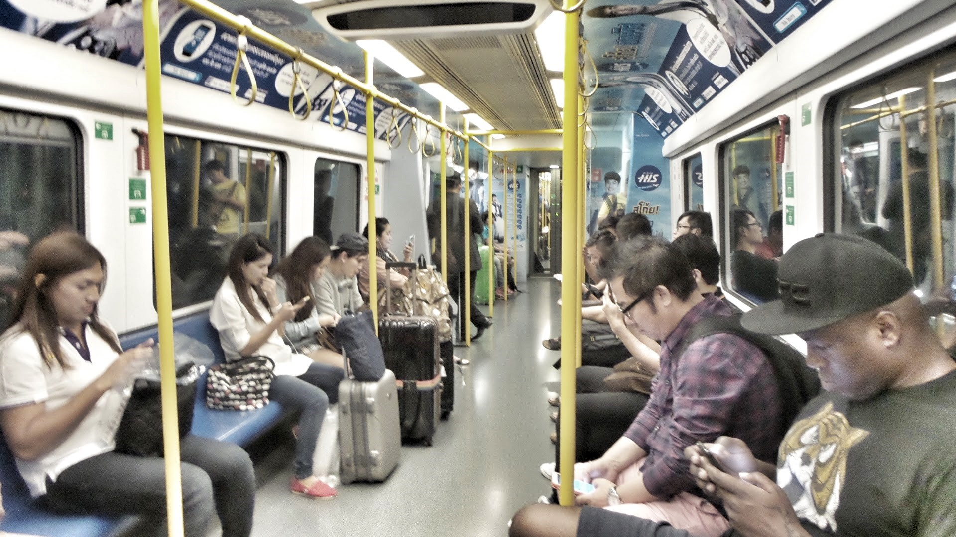 A subway car with all visible passengers looking at their smartphones