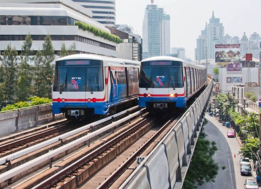 Two BTS SkyTrains pass each other at the Nana station on the Sukhumvit Line