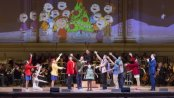 "Members of the TADA! Youth Theater with narrator John Bolton and music director Steven Reineke with the New York Pops and Essential Voices USA in the Carnegie Hall Family Concert ""A Charlie Brown Christmas"" (Photo credit: Richard Termine)"