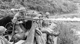 """Des soldats français essaient un lance-flamme sur une jeep blindée. Le """"Mapaly"""" peut être projeté à 120 m. Crédit : ECPAD."""