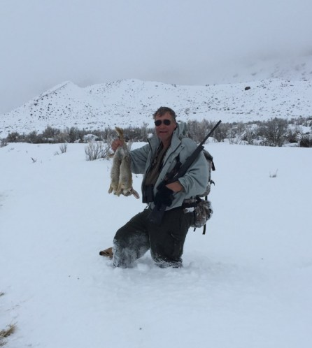 A hunter poses with a bag of mountain cottontail rabbit, taken with a .22 rifle in heavy snow in northwestern Colorado