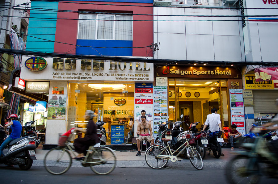 A busy street in Ho Chi Minh City where a man is getting a street massage as bikes ride by.