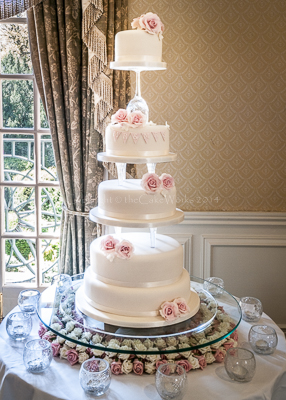 Four tier wedding cakes, pink roses and wine glass