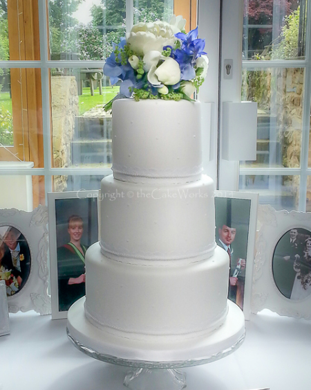 Three tier white wedding cake with fresh flower posy