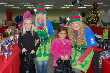 (From L to R) Cox Communications volunteers Melody Murray and Kathleen Sirbu, dressed in elf costumes, pose for a photo with Boys & Girls Club members Faith Coley and Jolene Merida. Courtesy photo