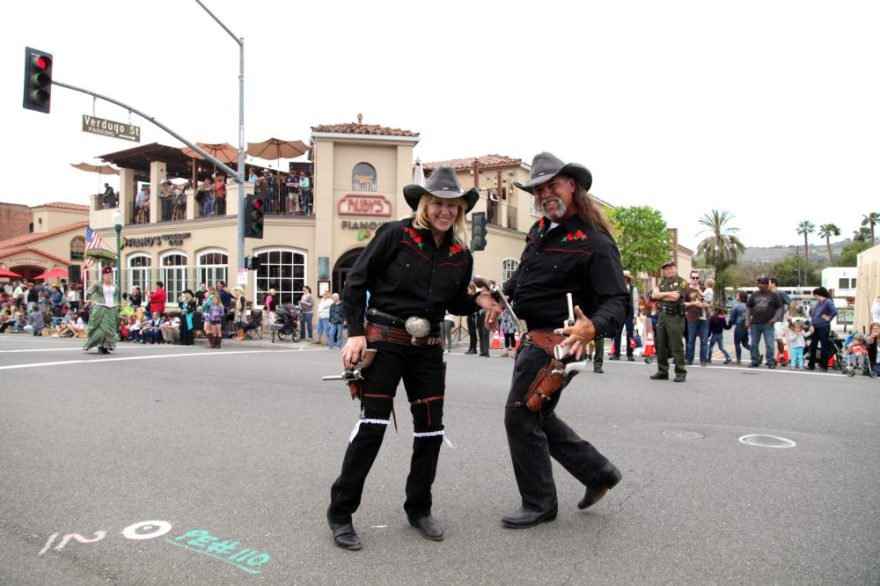 Leslie and Jim Leone, members of the 1880s reenactment group Spurs and Satin, show off their gun-spinning skills at the 2014 Swallows Day Parade. Photo: File