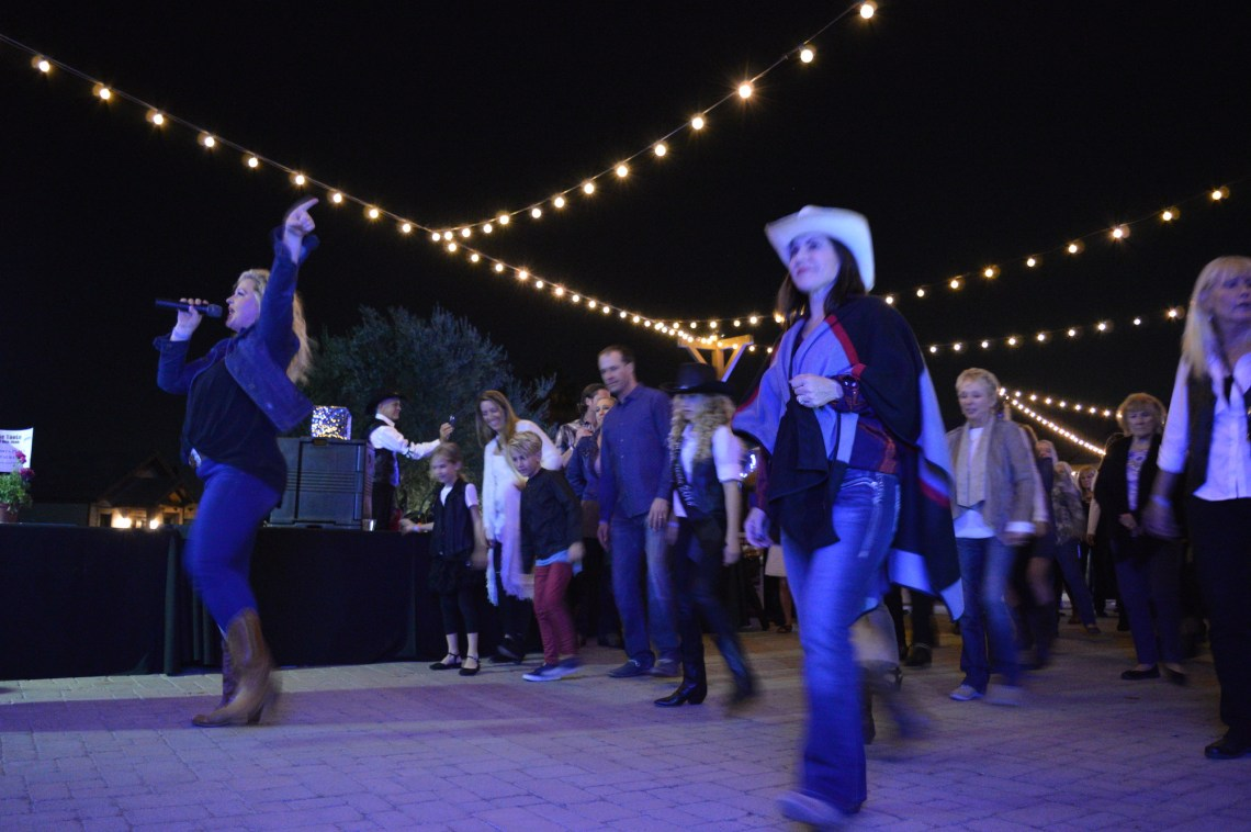 Attendees of The Taste of San Juan do the electric slide while listening to tunes from The Kelly Boyz Band. Photo: Emily Rasmussen