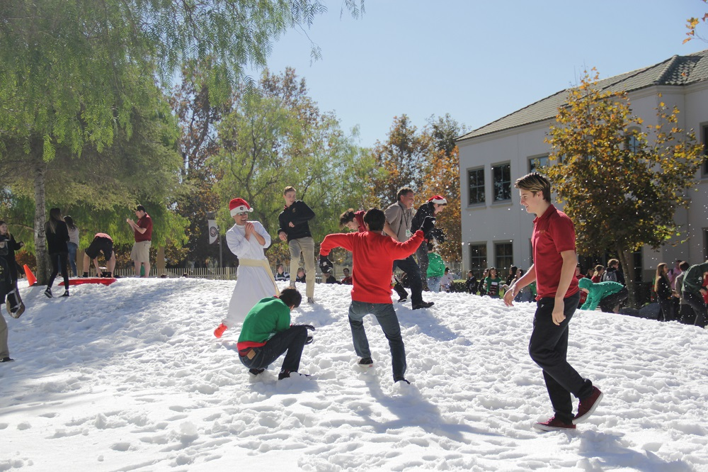 Festively rocking a Santa hat, Father Damien Giap gets in on the snowball action. Photo: Shawn Raymundo