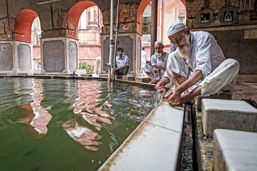 """A man performs """"wuzu"""" or ritual washing before prayers at the Nakhoda Masjid."""