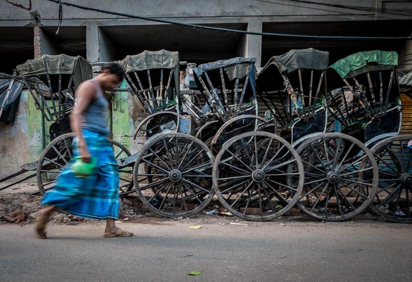 A resident walks past a line of pull rickshaws.