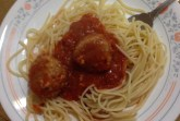 Vegan lentil balls served spaghetti and topped with marinara sauce.