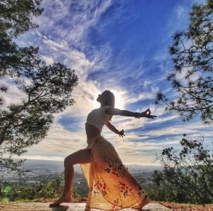 Krystal Aranyani practicing yoga in nature. Credit to Koi Fresco.