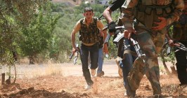 "Syrian rebels from the ""Al-Qasas Brigade"" or ""Justice Brigade"" run through an olive grove to avoid Syrian Army snipers as they travel between villages on foot in the northwestern Jabal al-Zawiya area."