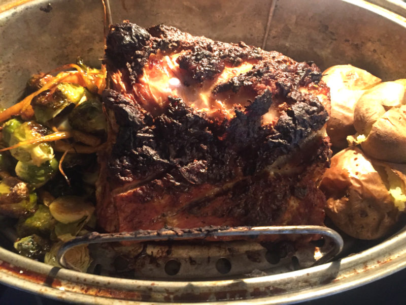 Pork roast served with baked potatoes and roasted Brussels sprouts and carrots medly