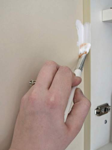 Use an artist's brush to paint the cabinet frame and edges without needing to tape the interior of every cabinet - The Handyman's Daughter