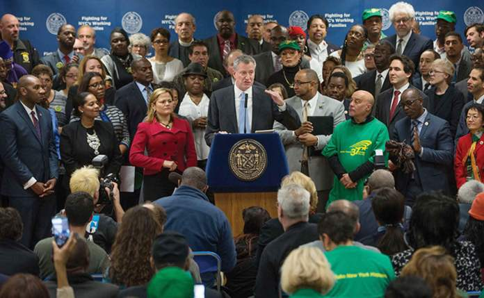 New York City Mayor Bill de Blasio announced, January 6, guaranteed $15 minimum wage for all City government employees. Council Speaker Mark Viverito is seen to the right of the Mayor Photo courtesy Mayor's Office
